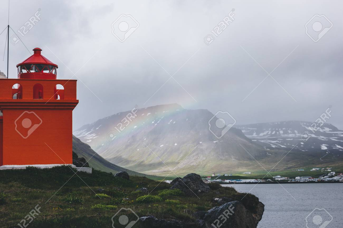 red lighthouse on cliff with rainbow on background in Iceland