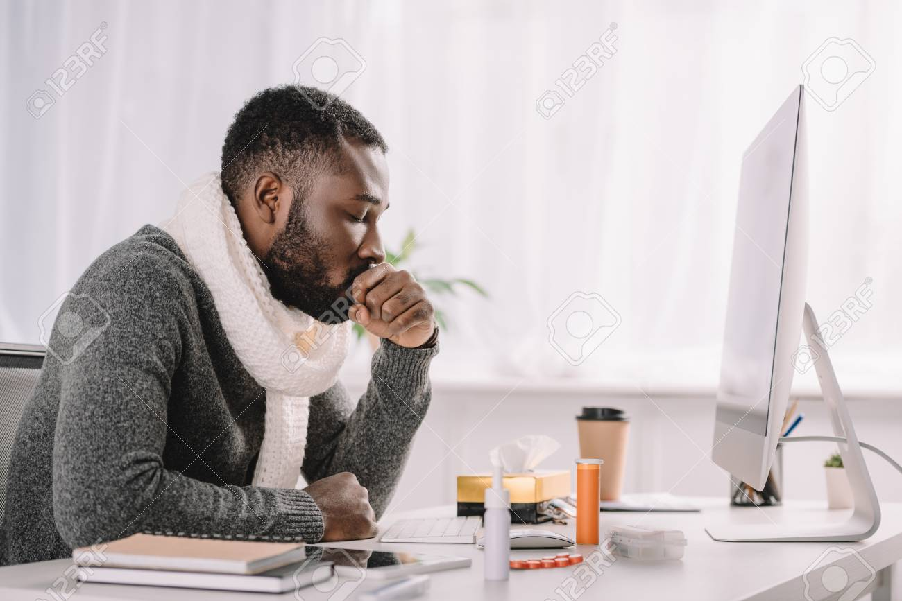 Diseased African American businessman coughing at work space with medicines - 110349352