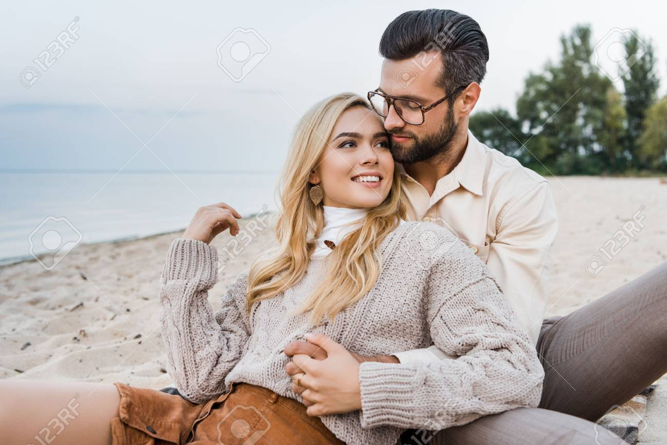 Smiling girlfriend and boyfriend in autumn outfit sitting and hugging on beach - 110357948