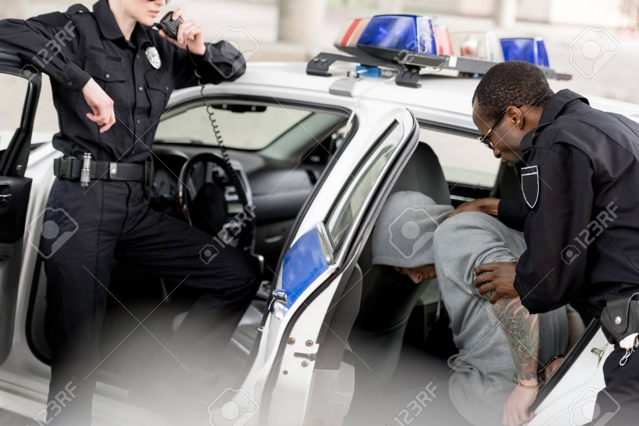 cropped shot of policewoman talking on radio set while her partner placing arrested man in car - 110739491