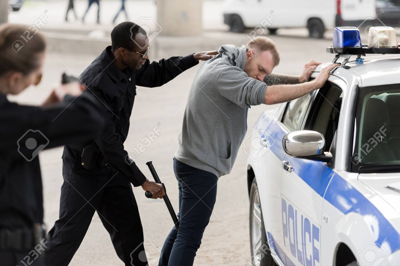 side view of african american arresting man while policewoman aiming at him by handgun - 110782186