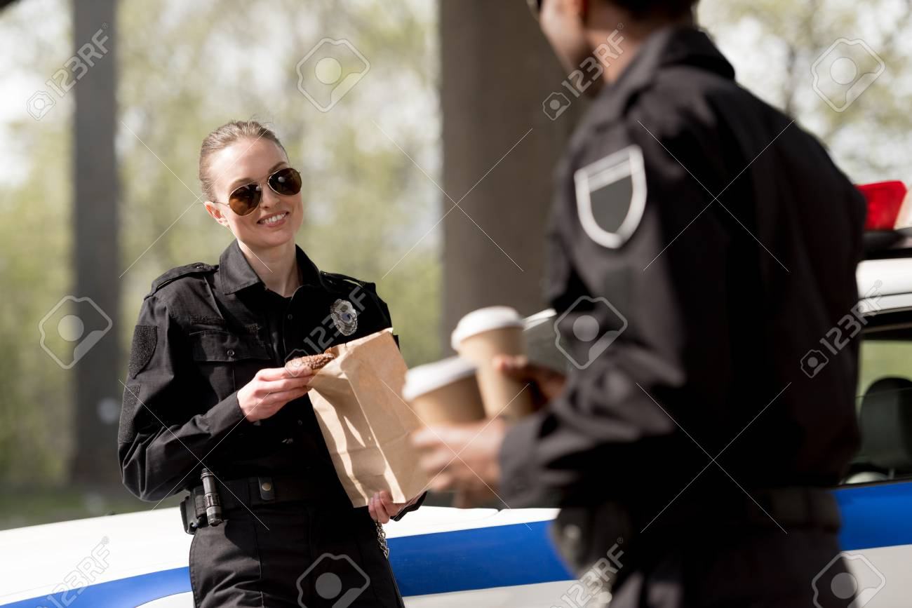 police officers with coffee to go and paper bag with lunch having
