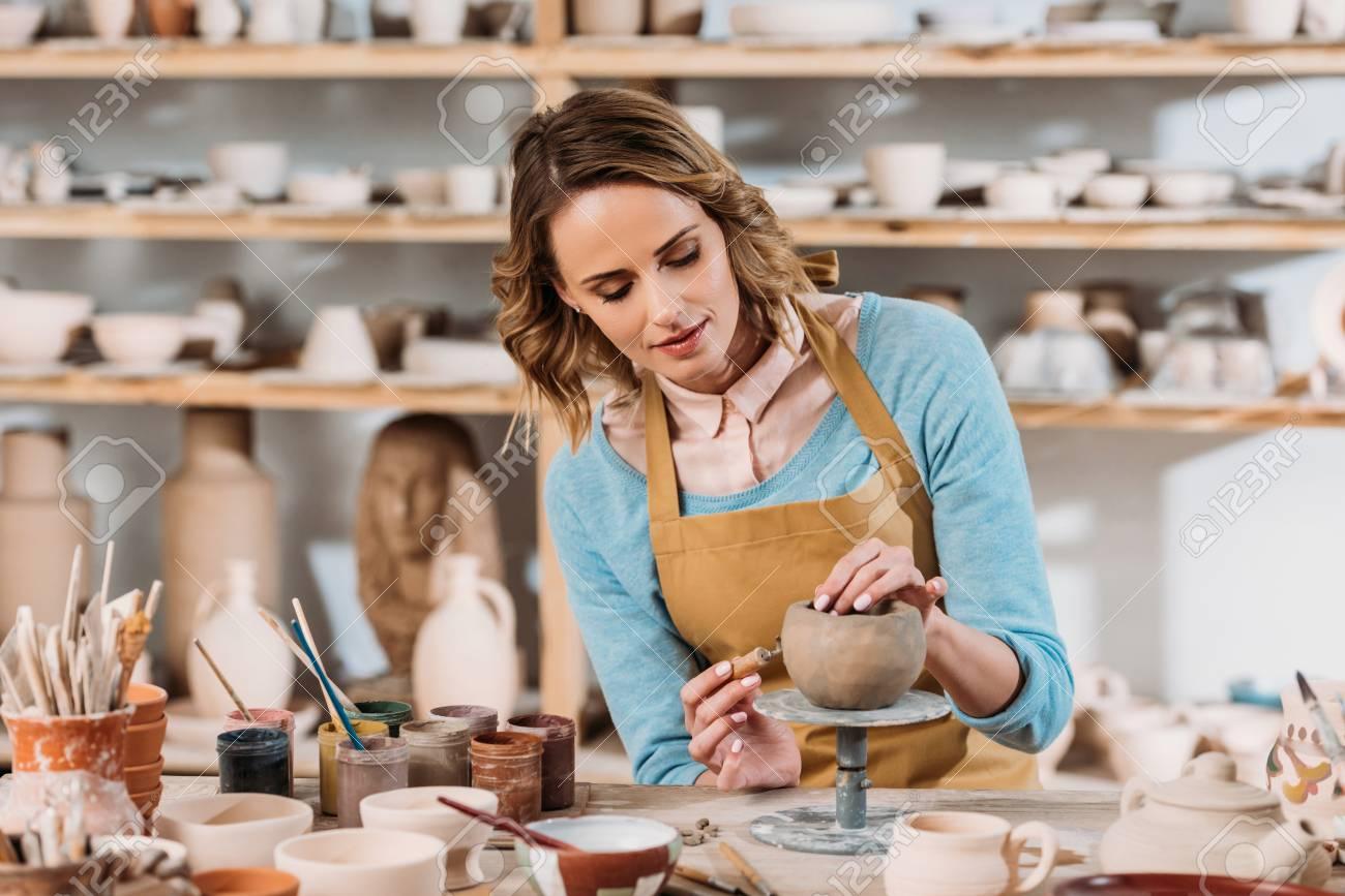 Beautiful female potter decorating ceramic bowl in workshop - 111004565