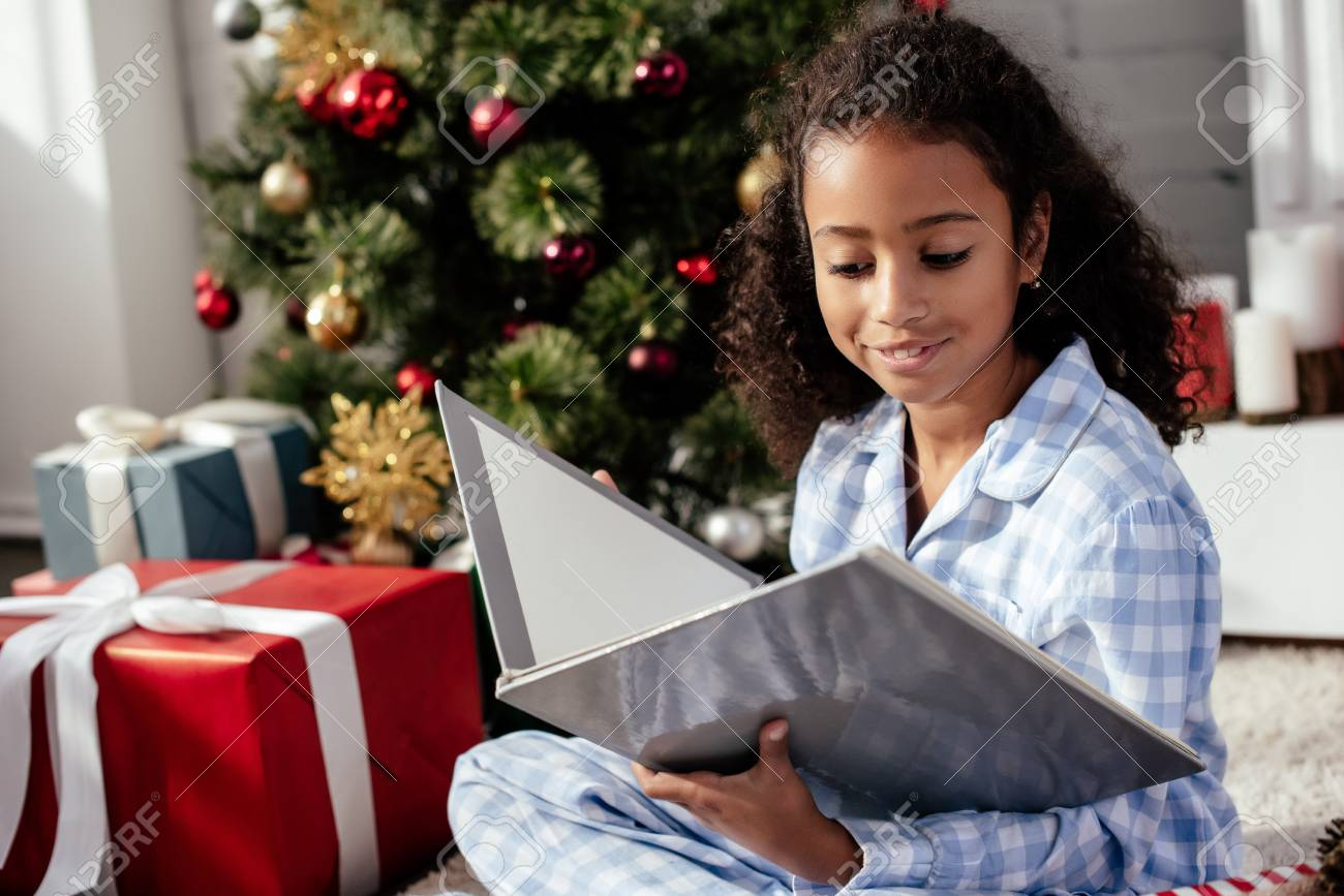 68402d015333 Cheerful adorable African American child in pajamas reading book near  Christmas tree at home Stock Photo