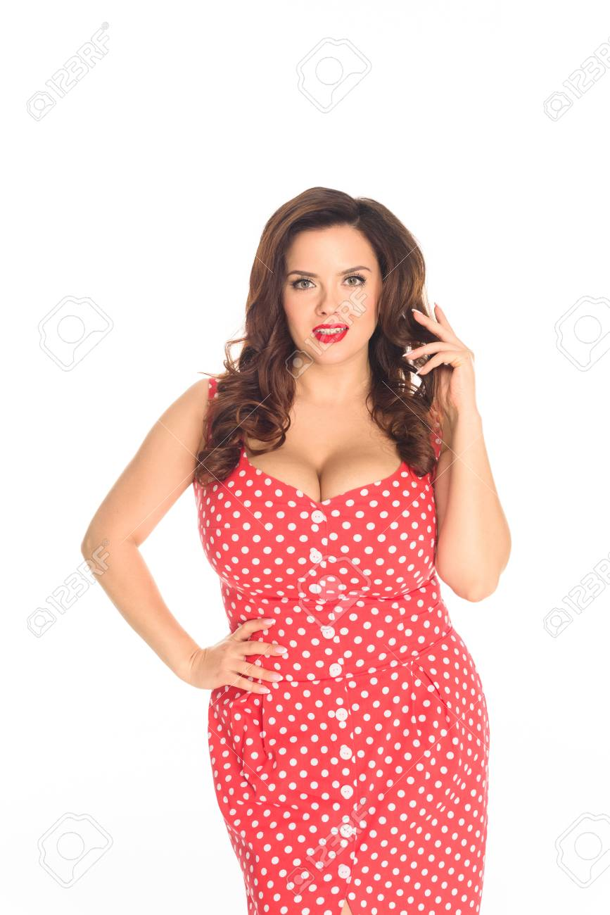 Beautiful plus size woman in red dotted dress looking at camera..