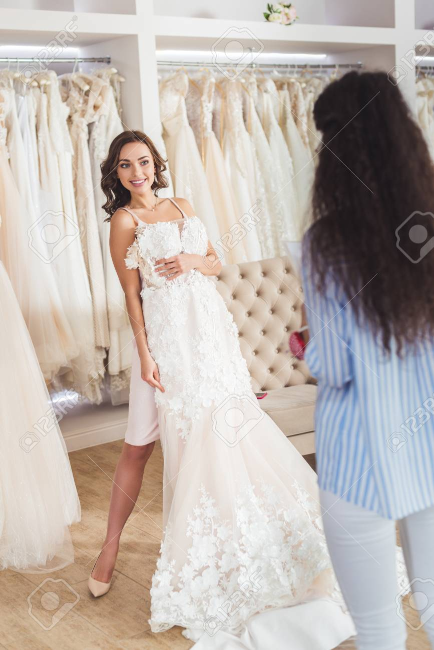 Female Tailor By Bride Trying On Wedding Dress In Wedding Salon