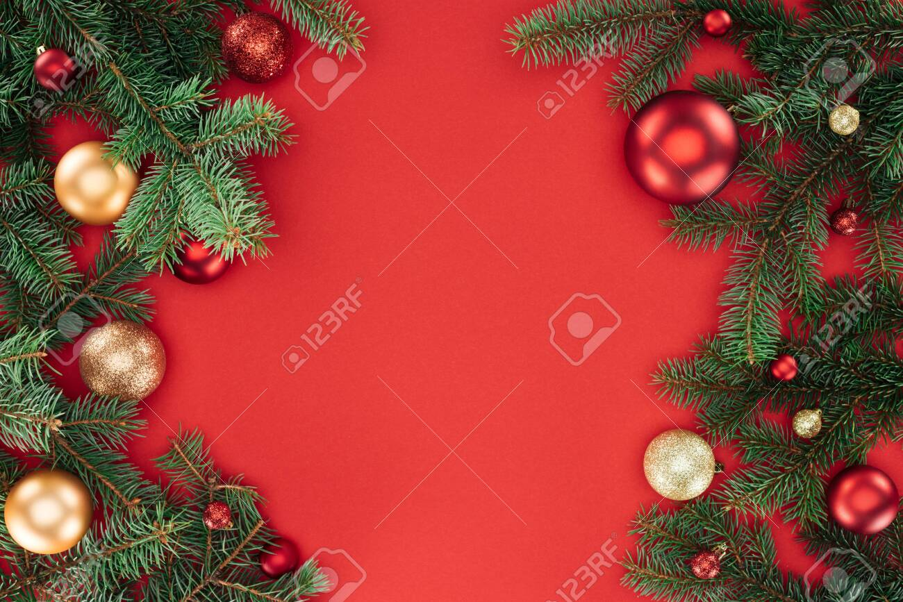 flat lay with pine tree branches with red and golden christmas balls isolated on red - 112125743