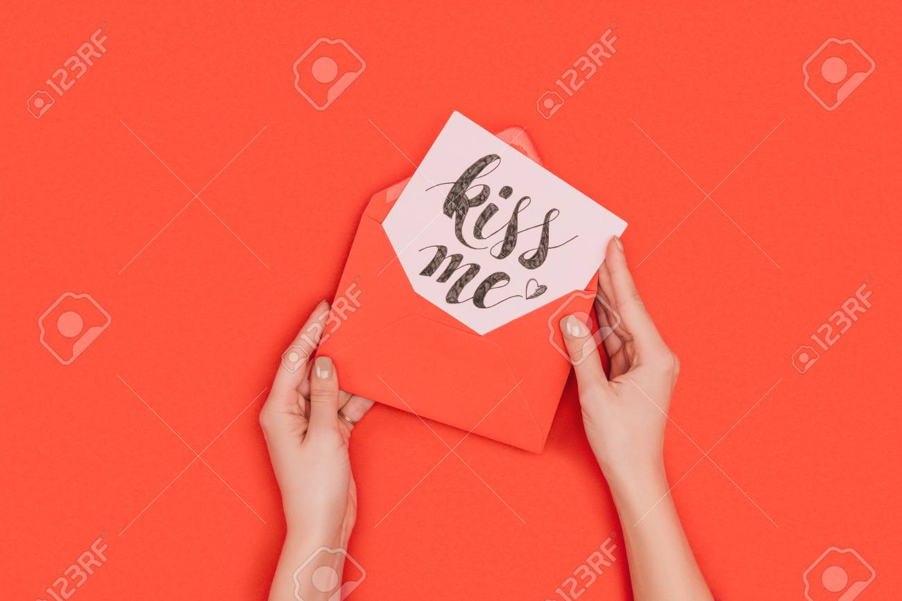 cropped shot of person holding red envelope with card and kiss me inscription isolated on red - 112269695