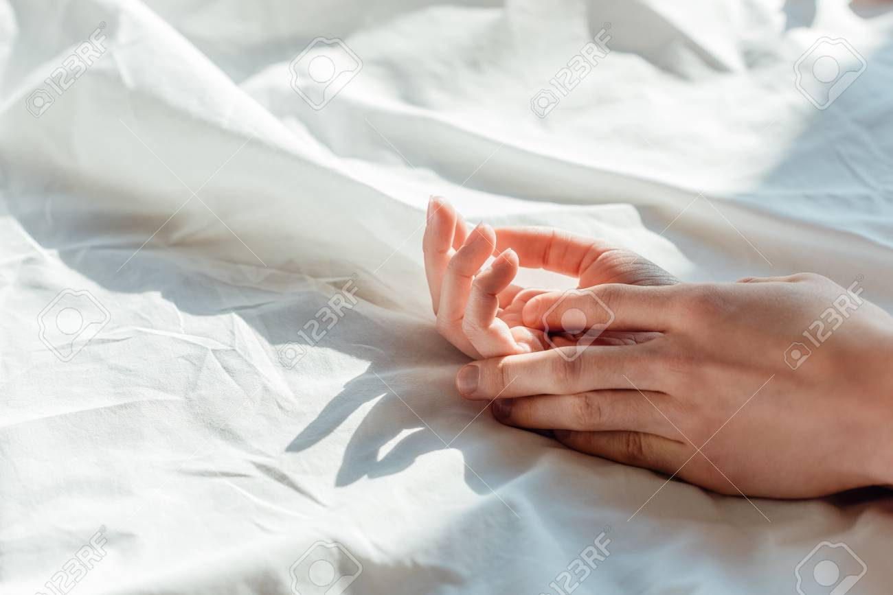 Partial View Of Couple In Live Holding Hands While Lying In Bed ...