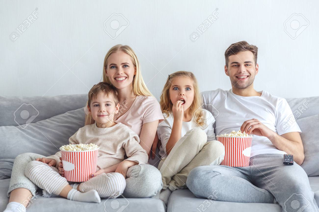 Excited Young Family Watching Movie On Couch At Home Stock Photo, Picture  And Royalty Free Image. Image 111736484.