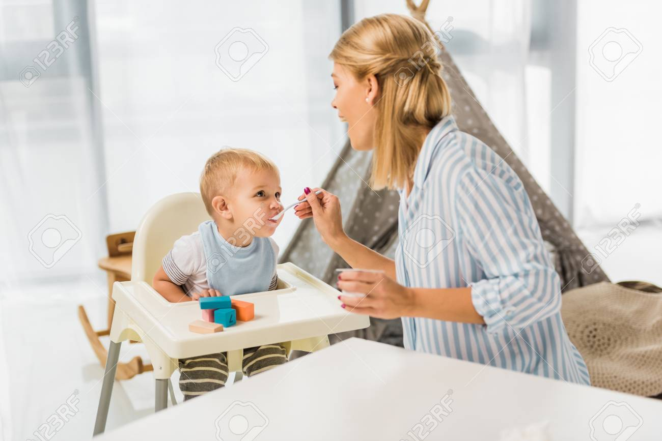 Mom feeding son in highchair with baby food - 112274403