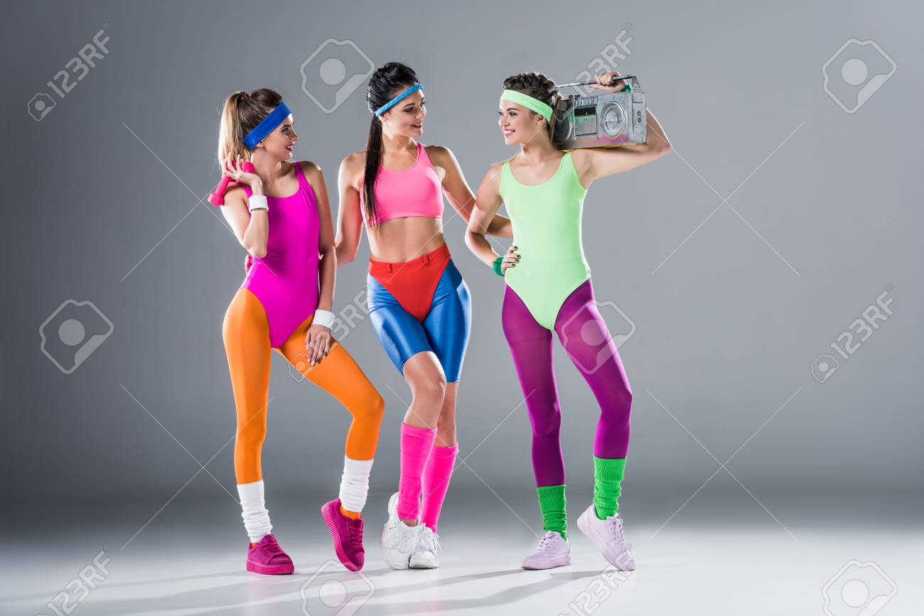 attractive sporty girls with dumbbells and tape recorder smiling each other on grey - 111786523