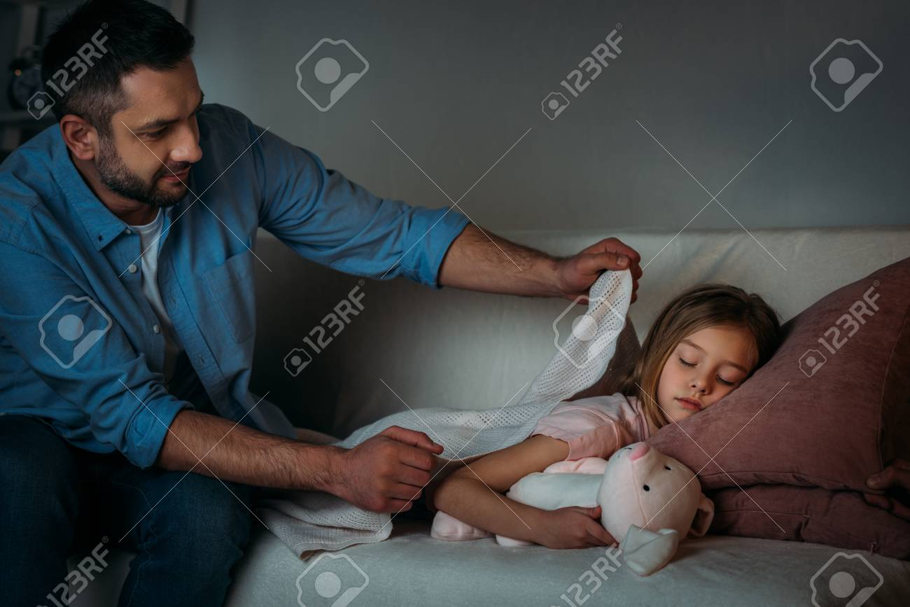 father covering sleeping daughter with blanket - 111819353