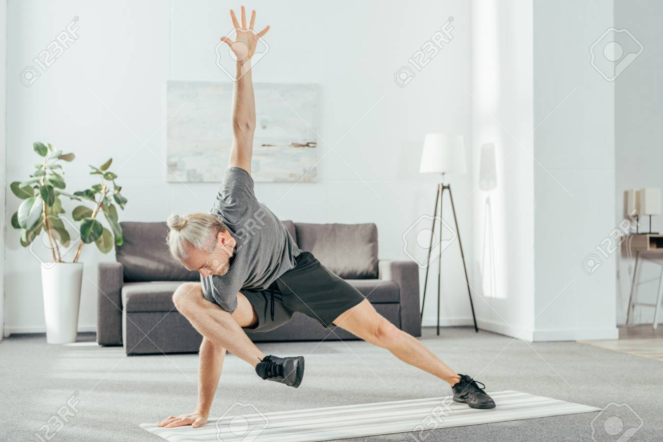 2a3d360e1c63 flexible sporty man exercising on yoga mat at home Stock Photo - 112158851