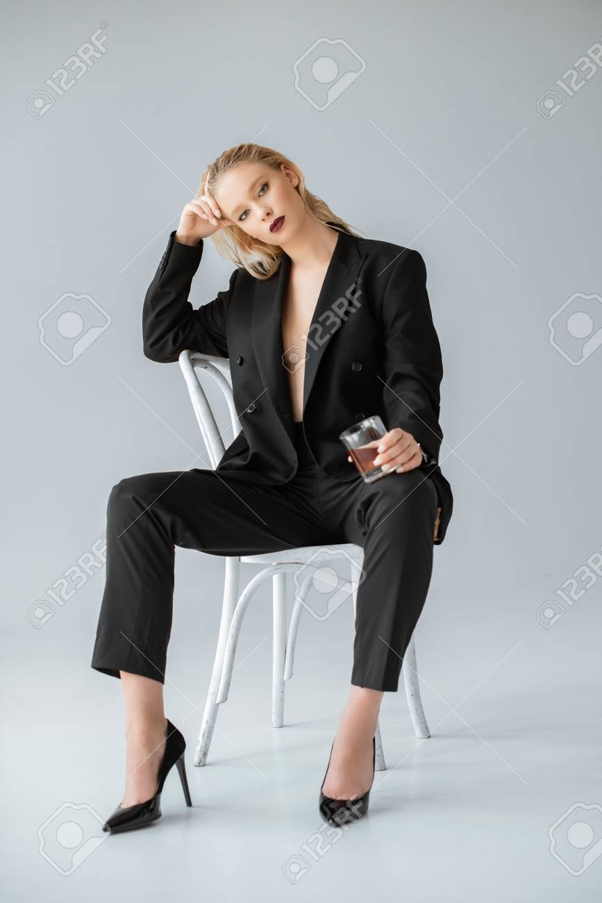 fashionable woman in formal wear with glass of whiskey sitting on chair on grey - 112333602