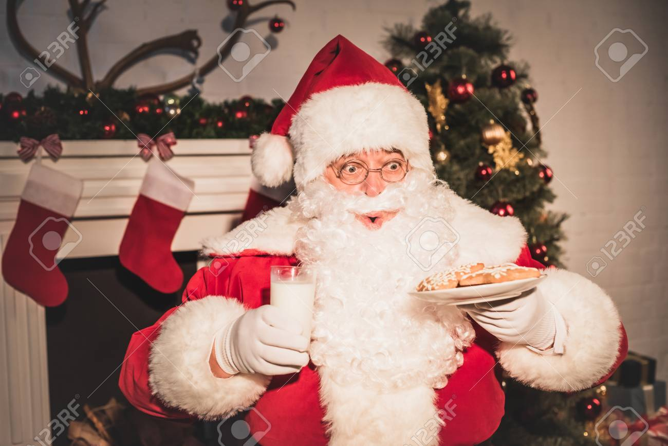 Emotional Santa Holding Plate With Cookies And Glass Of Milk