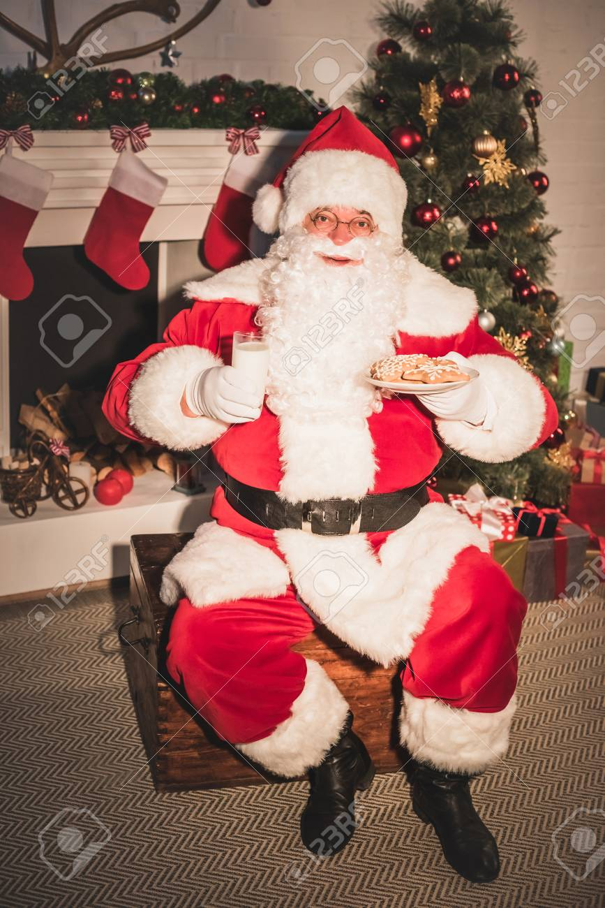 Santa Claus Holding Plate With Cookies And Glass Of Milk