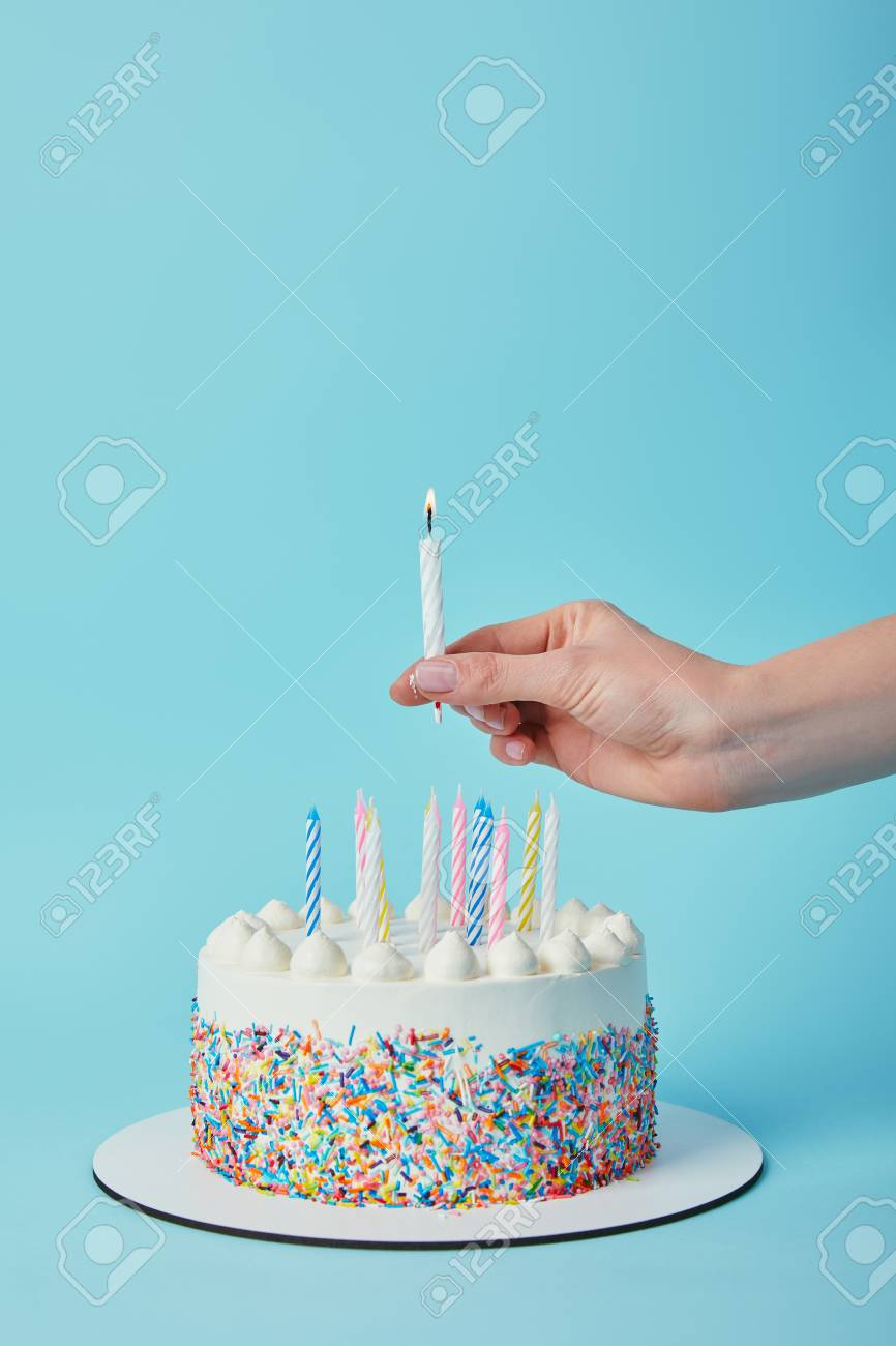 Partial View Of Woman Putting Lighting Candle On Birthday Cake Blue Background Standard Bild