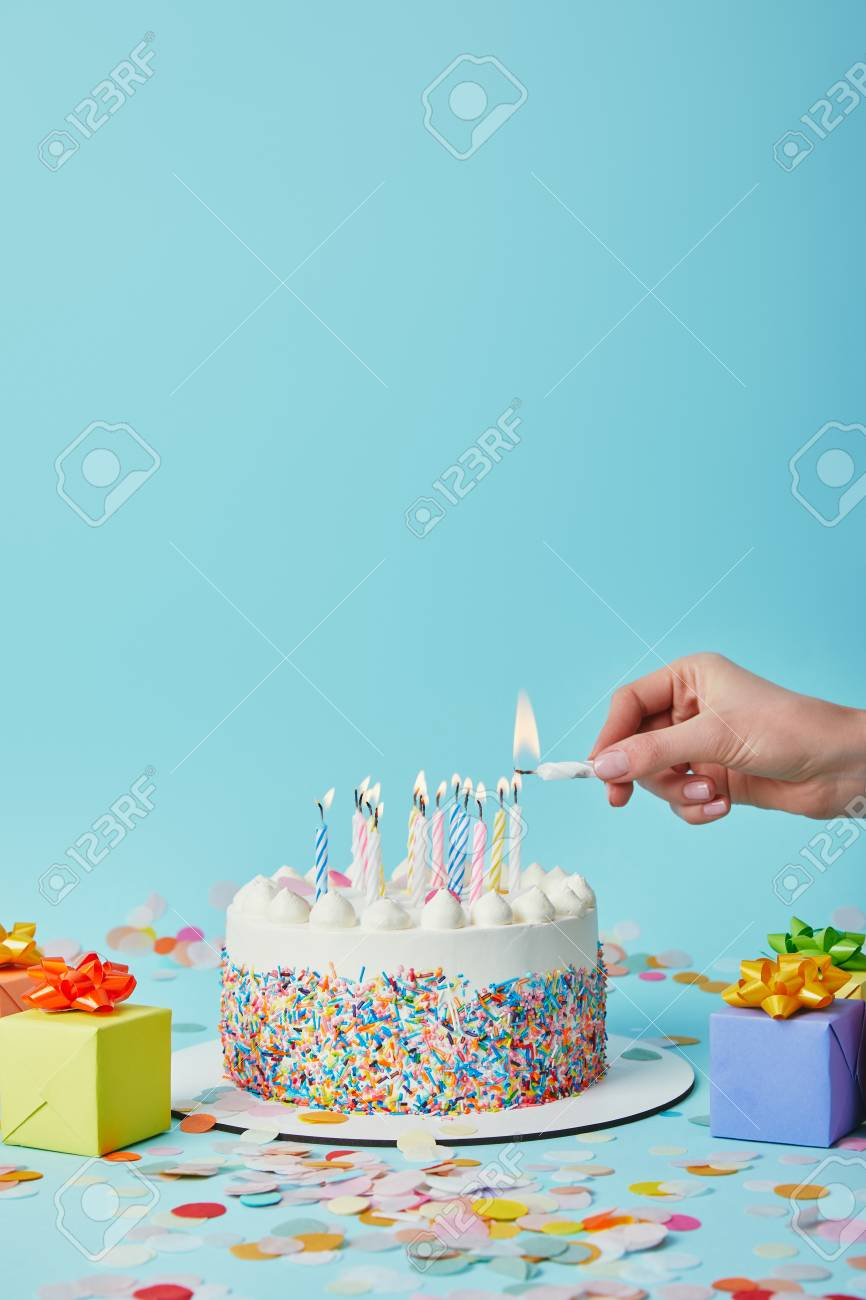 Partial View Of Woman Lighting Birthday Cake On Blue Background With Gifts And Confetti Stock Photo