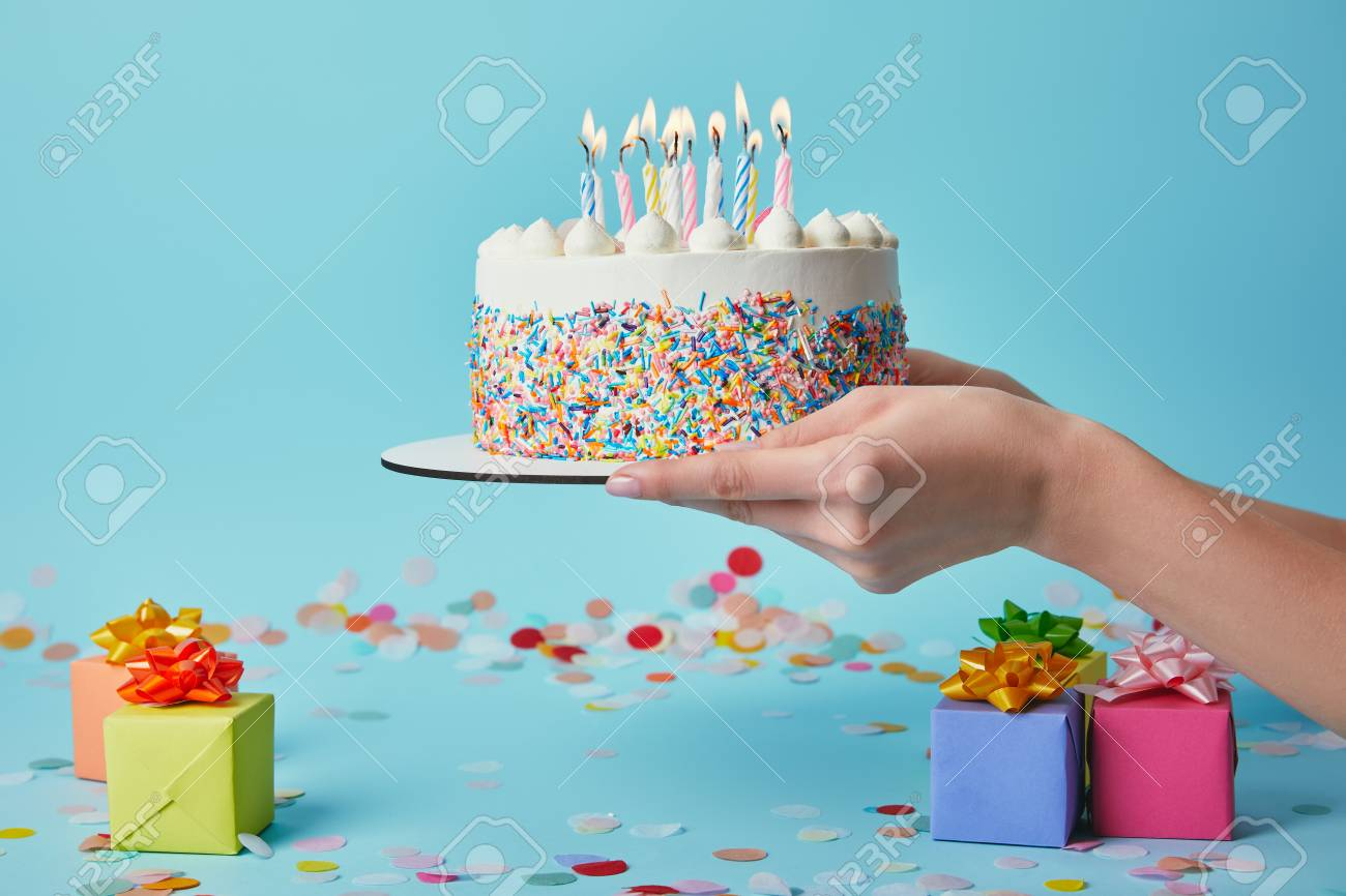 Cropped View Of Woman Holding Birthday Cake With Candles On Blue Background Confetti And Gifts