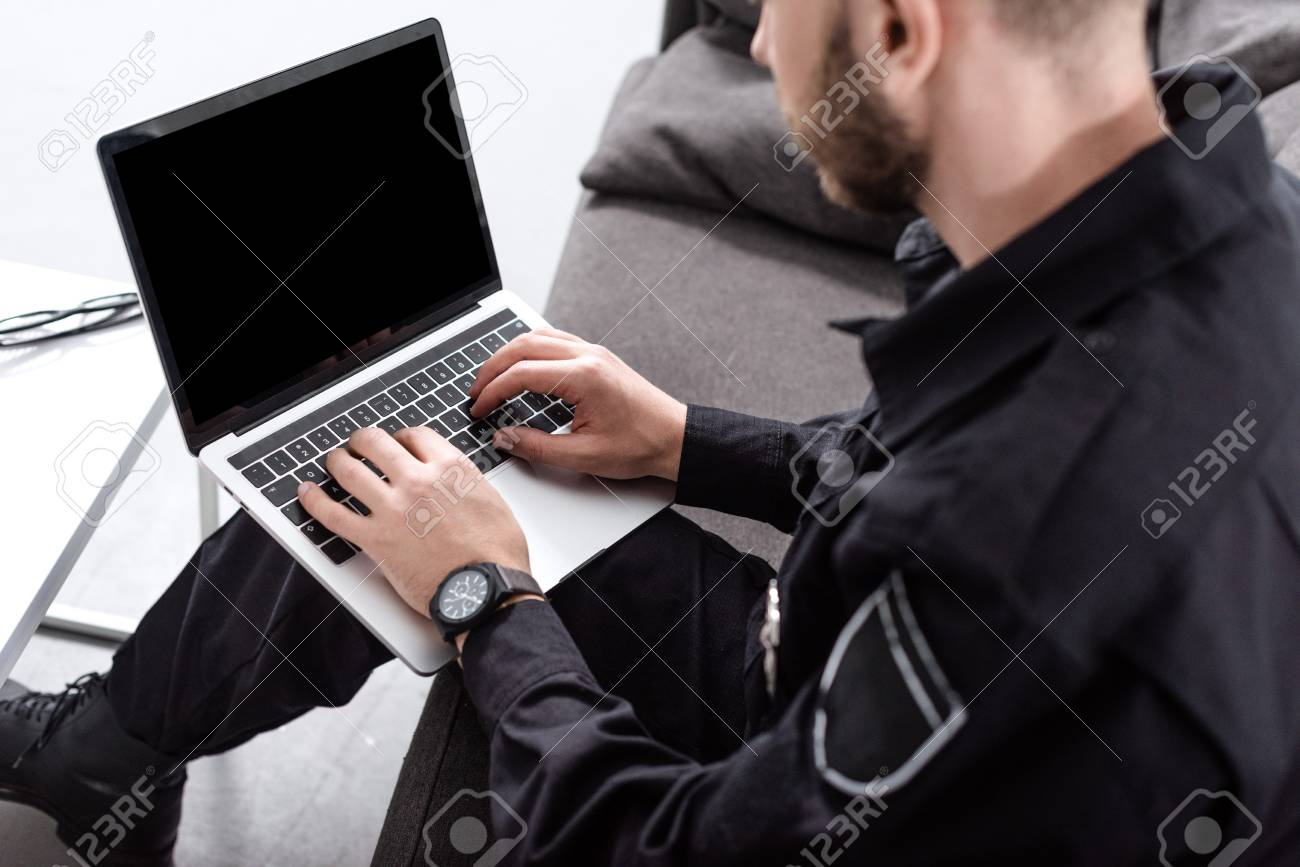 Cropped view of police officer sitting on couch and typing on laptop keyboard - 112757953