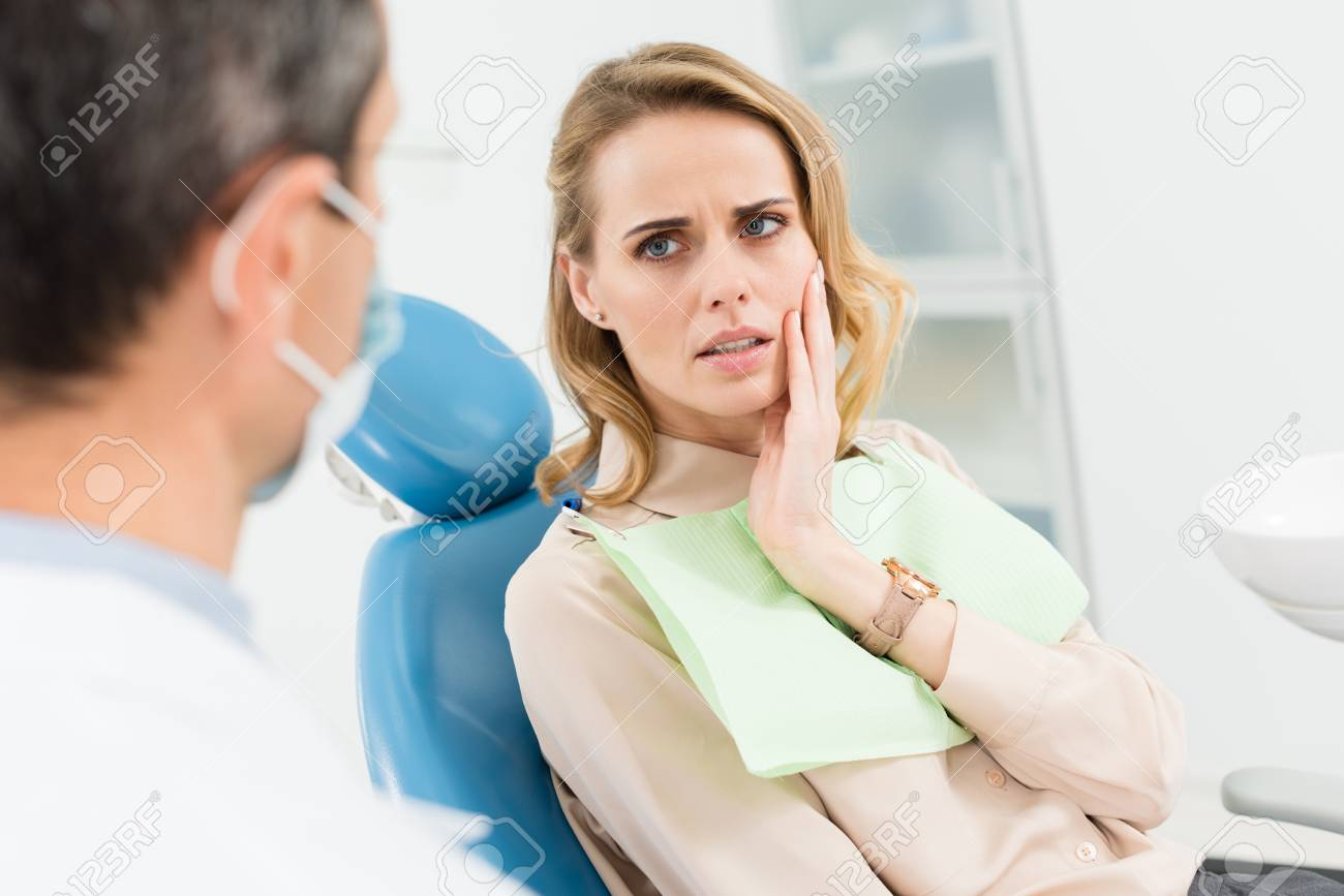 Female patient concerned about toothache in modern dental clinic - 112761008