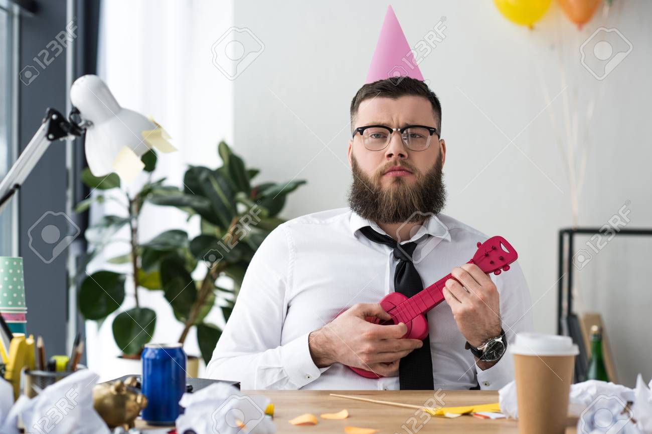 portrait of businessman with party cone on head and toy guitar at workplace in office - 112756483