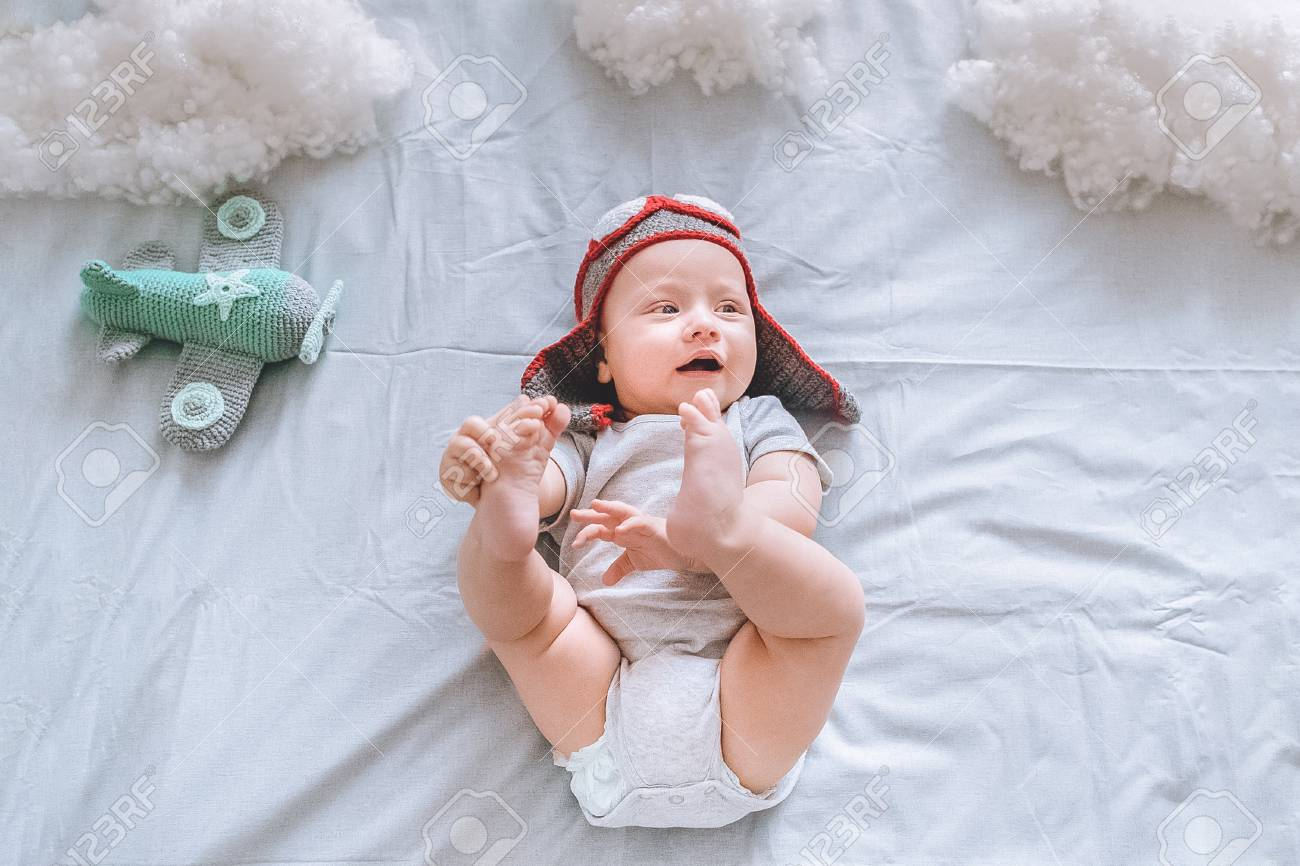 bebf3f082 top view of dreamy infant child in pilot hat with toy plane surrounded..
