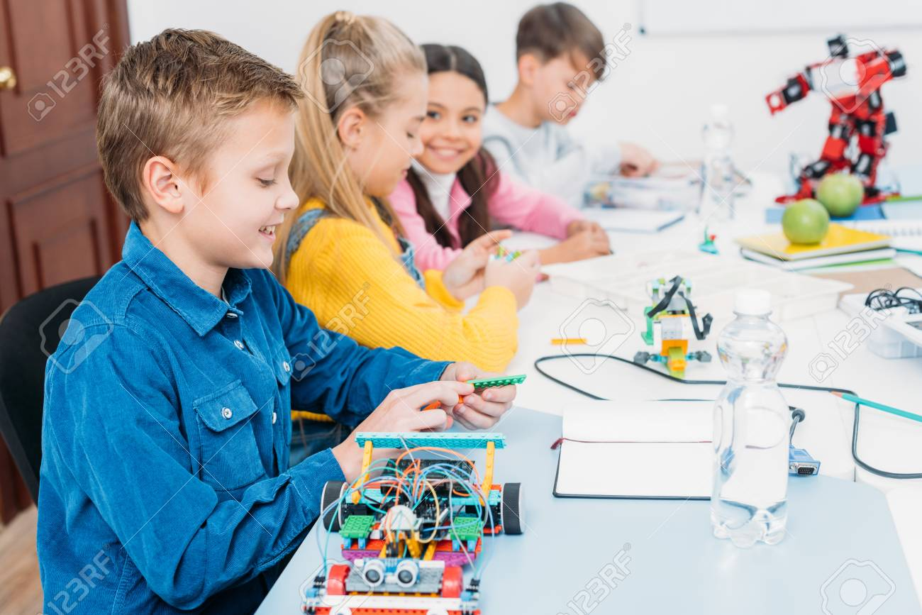 happy children sitting at desk and making robots in stem education class - 112988522