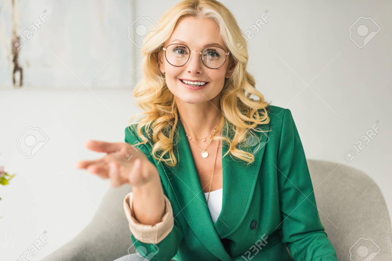 smiling middle aged businesswoman in eyeglasses looking at camera and gesturing with hand while sitting in armchair - 114324083