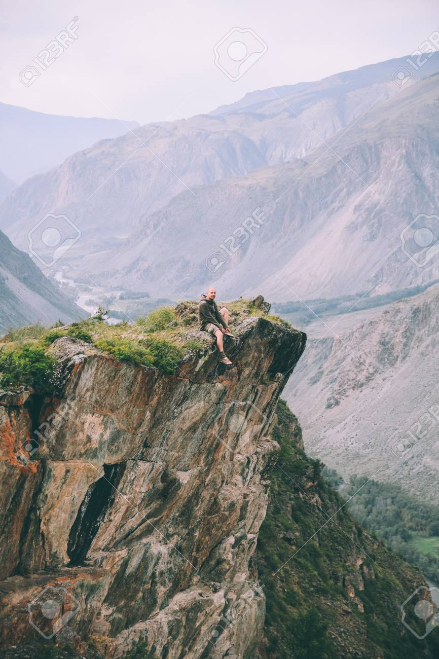 man sitting on cliff and looking at majestic mountains in Altai, Russia - 114328263