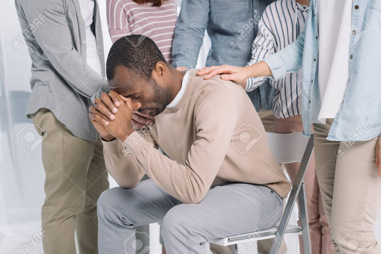 cropped shot of people supporting depressed middle aged african american man during group therapy - 114549593