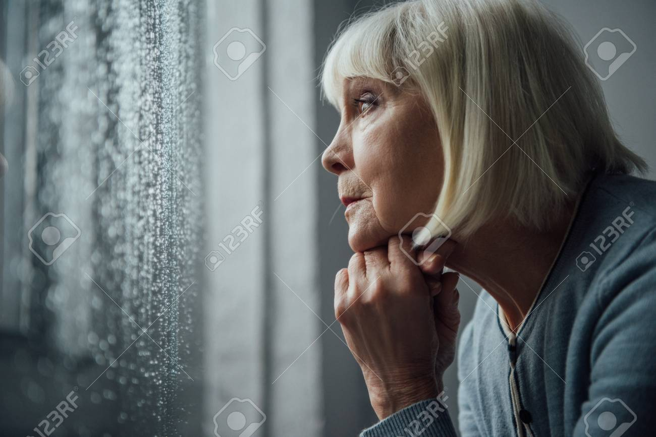 senior woman with grey hair propping chin with hand and looking through window with raindrops at home - 116322430