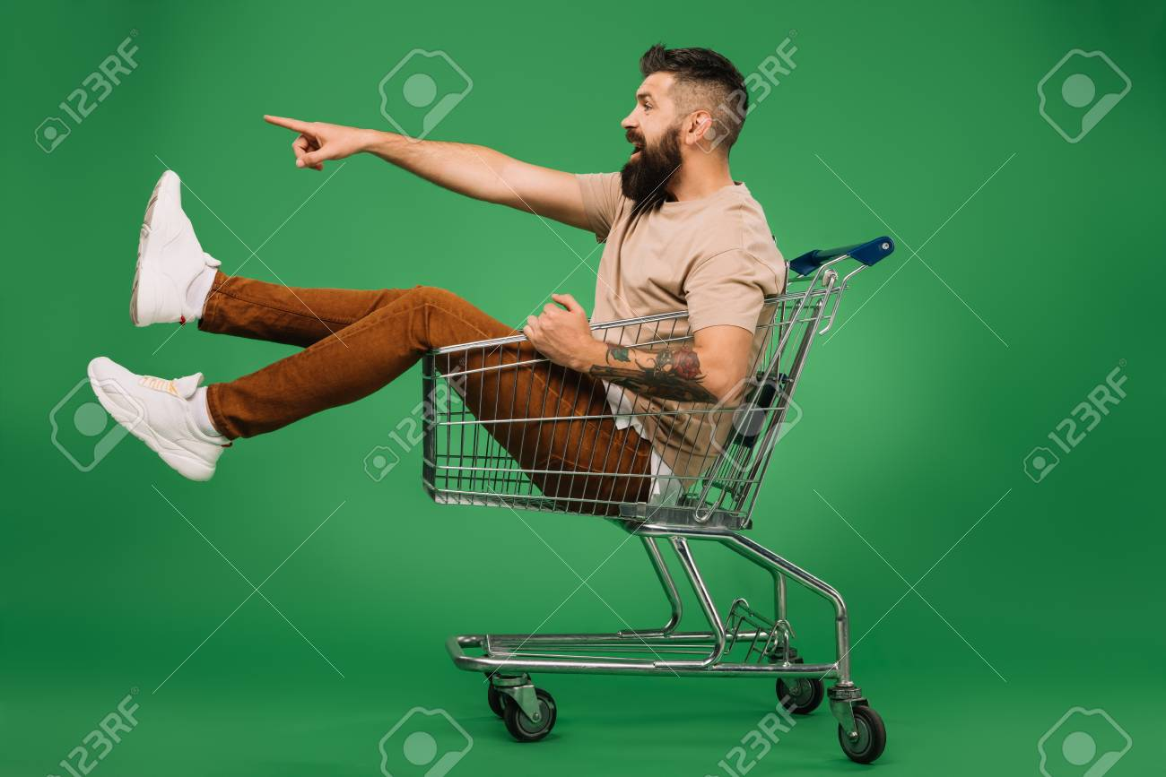 excited bearded man showing something while sitting in shopping cart isolated on green - 116424275