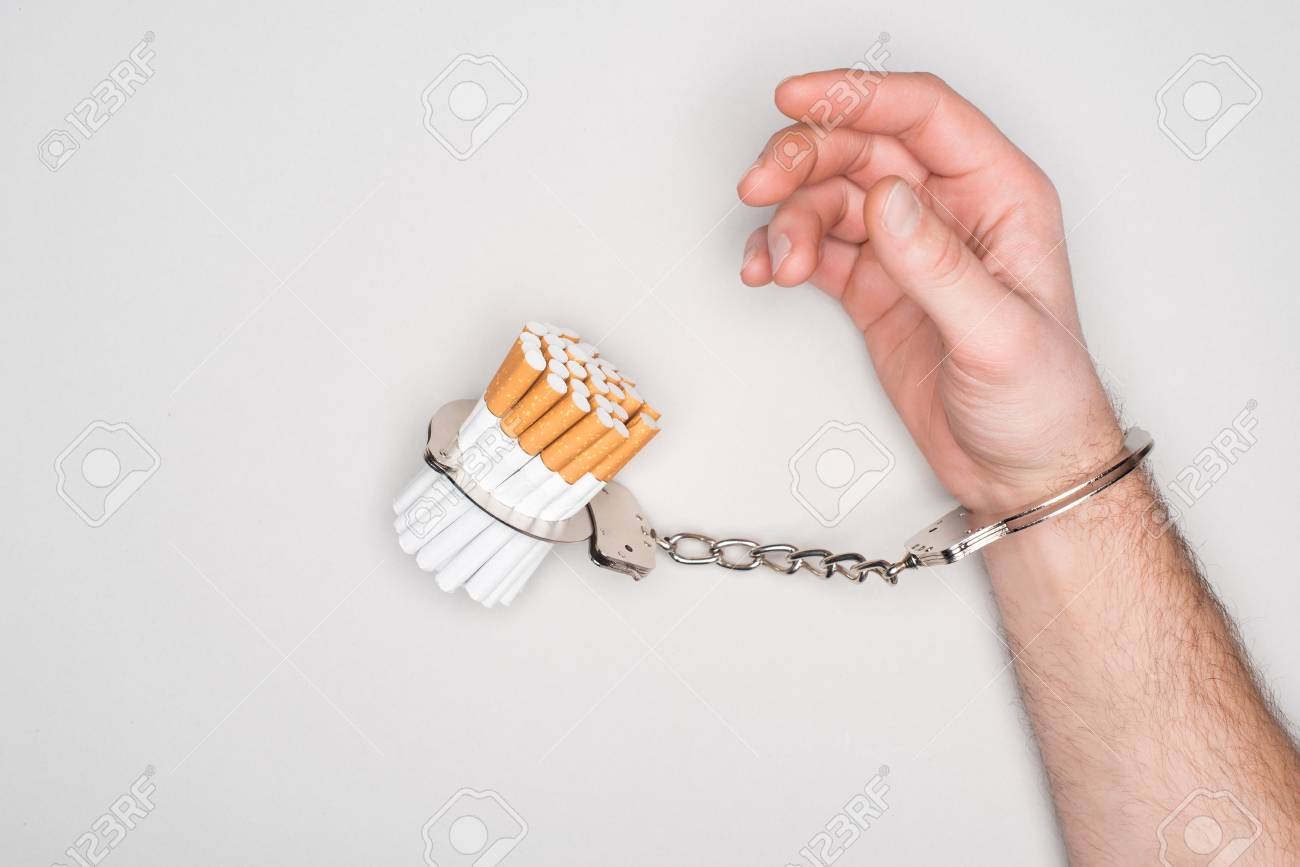 Partial view of man in handcuffs posing with cigarettes isolated on grey, nicotine addiction concept - 116592802