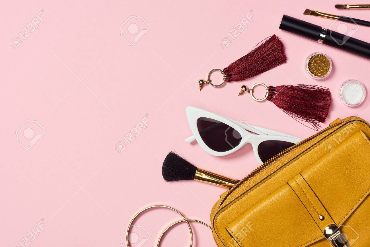 Top view of bracelets, earrings, sunglasses, mascara, cosmetic brushes, eyeshadow and bag on pink background - 116494308