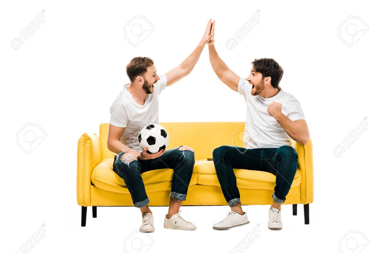 happy young man sitting on couch with soccer ball and giving high five isolated on white - 117782050