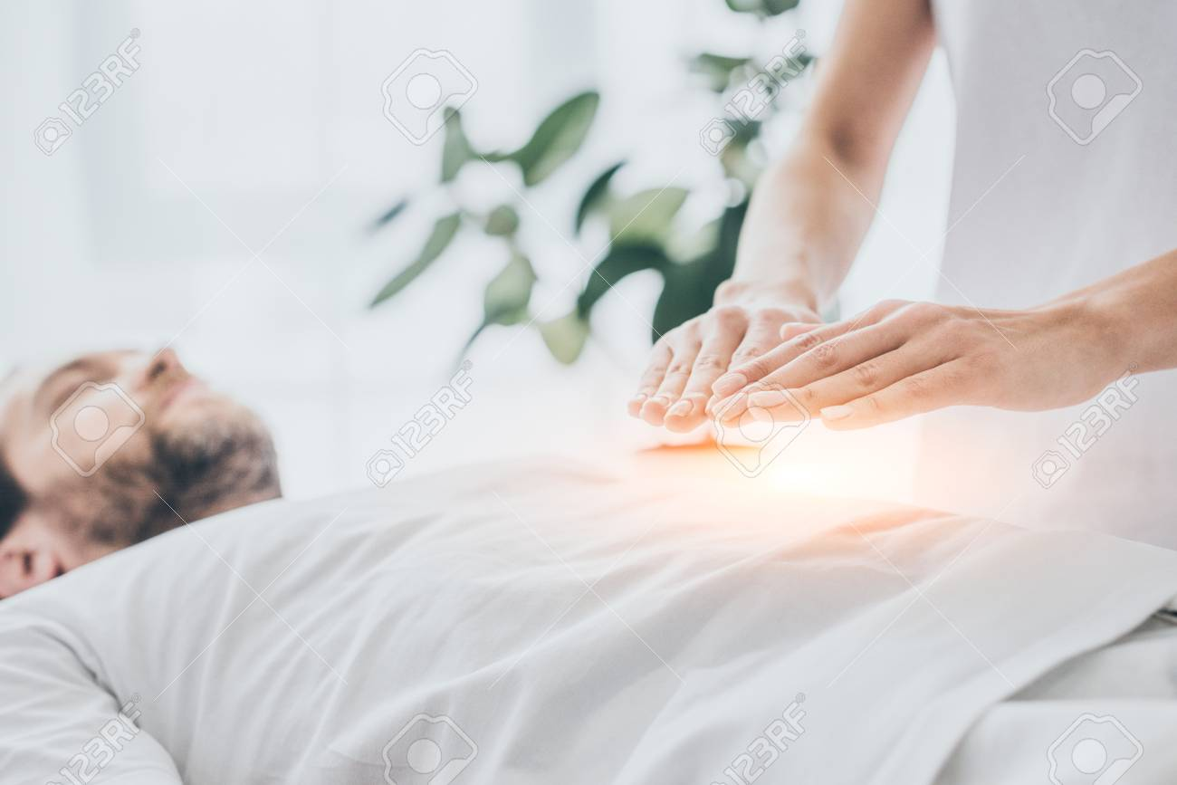 cropped shot of man receiving reiki treatment on stomach - 117857624
