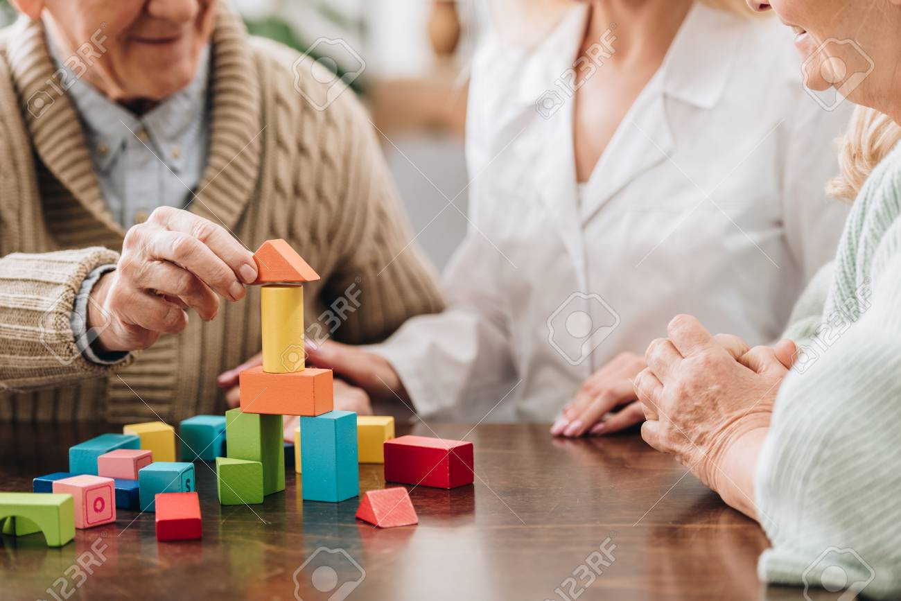 cropped view of caregiver sitting with retired man and woman and playing with wooden toys - 117439376