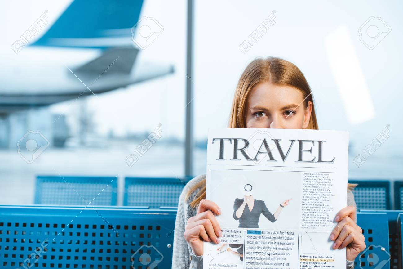 Airline Milf woman holding travel newspaper in waiting hall in airport