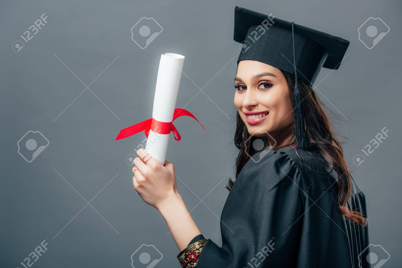 smiling female indian student in academic gown and graduation cap holding diploma, isolated on grey - 117398262