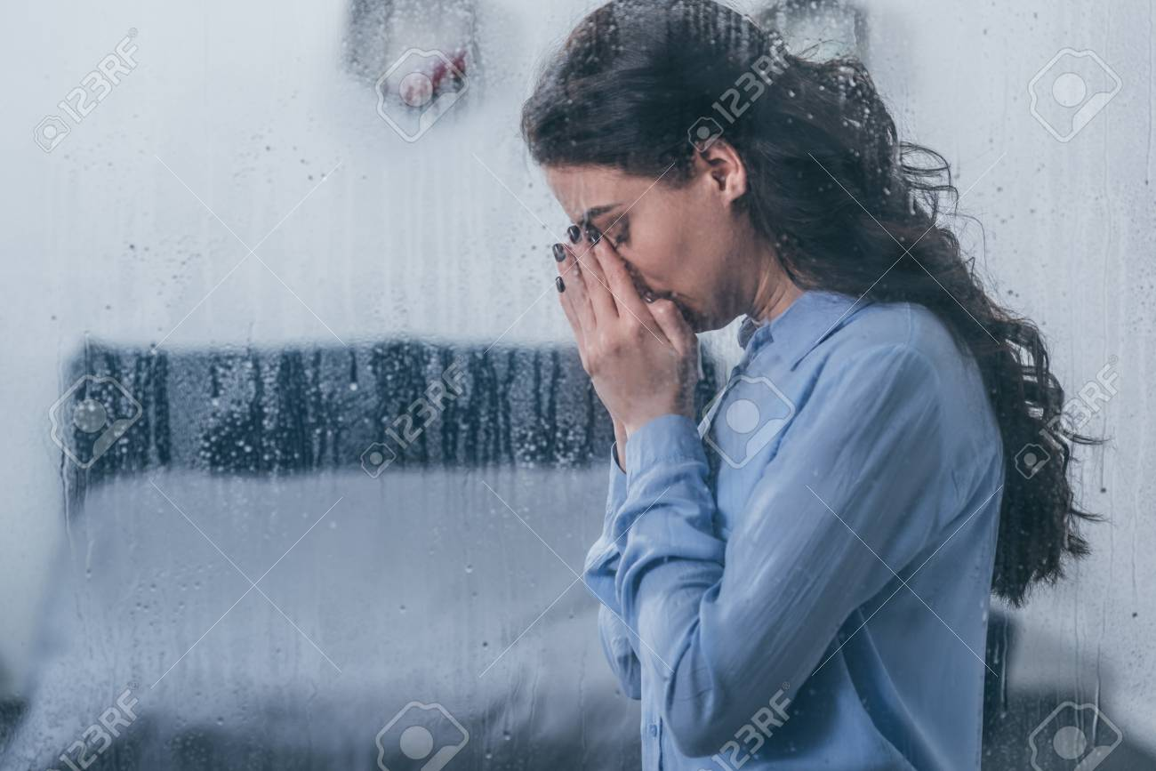 depressed woman covering face with hands and crying at home through window with raindrops and copy space - 117397613