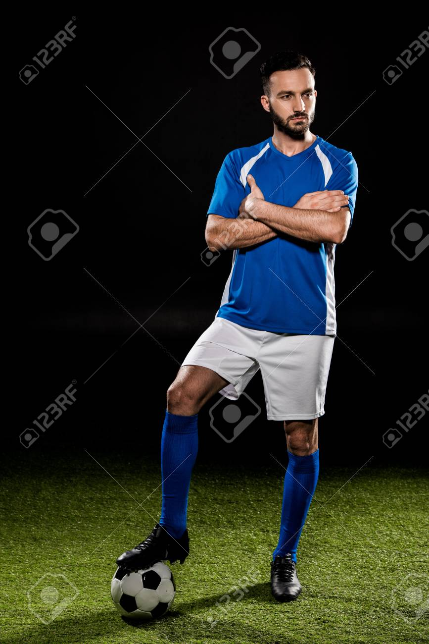 bearded football player standing with ball with crossed arms isolated on black - 117910560