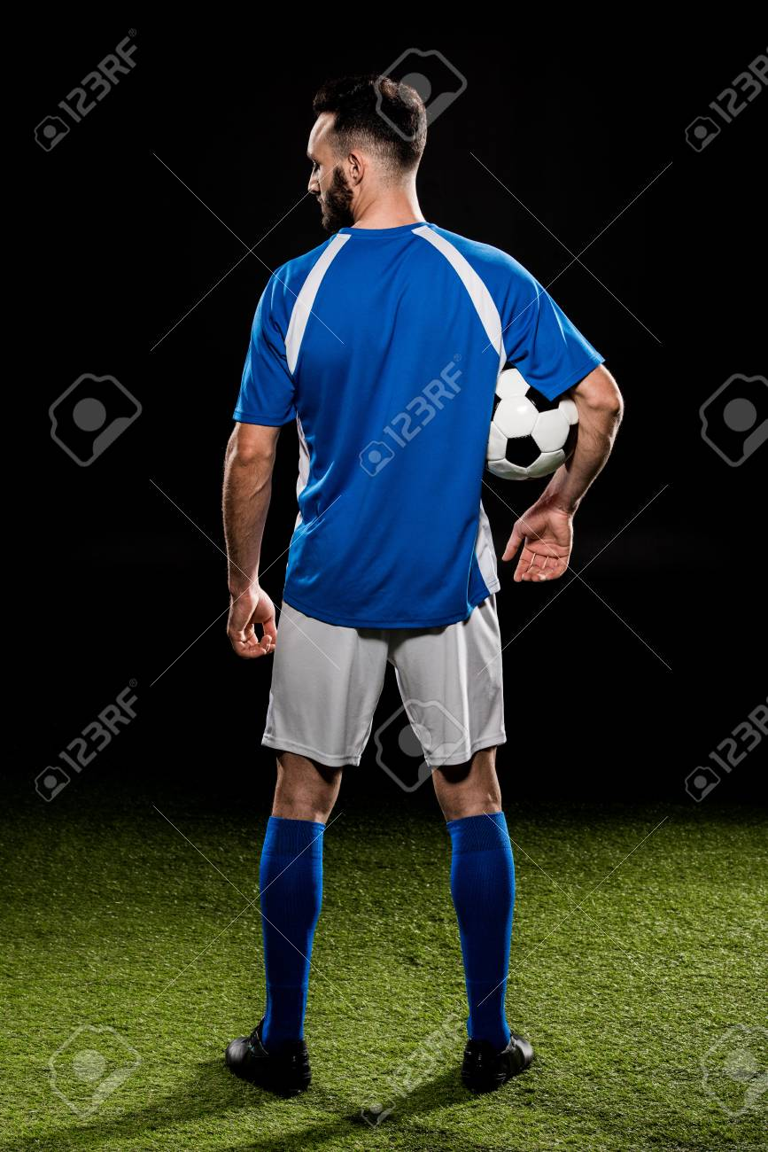 muscular sportsman in uniform holding ball isolated on black - 117910567