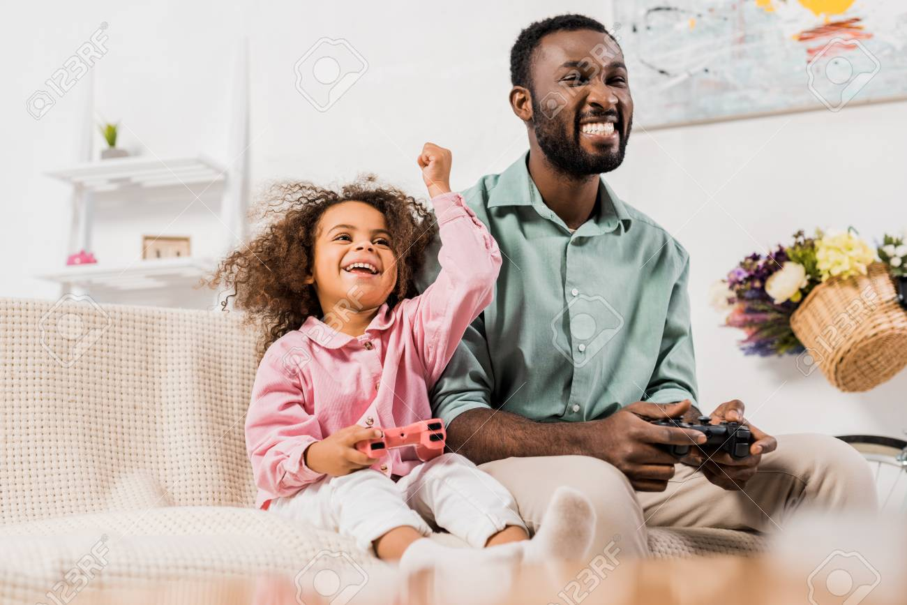 african american dad laughing with daughter and playing video