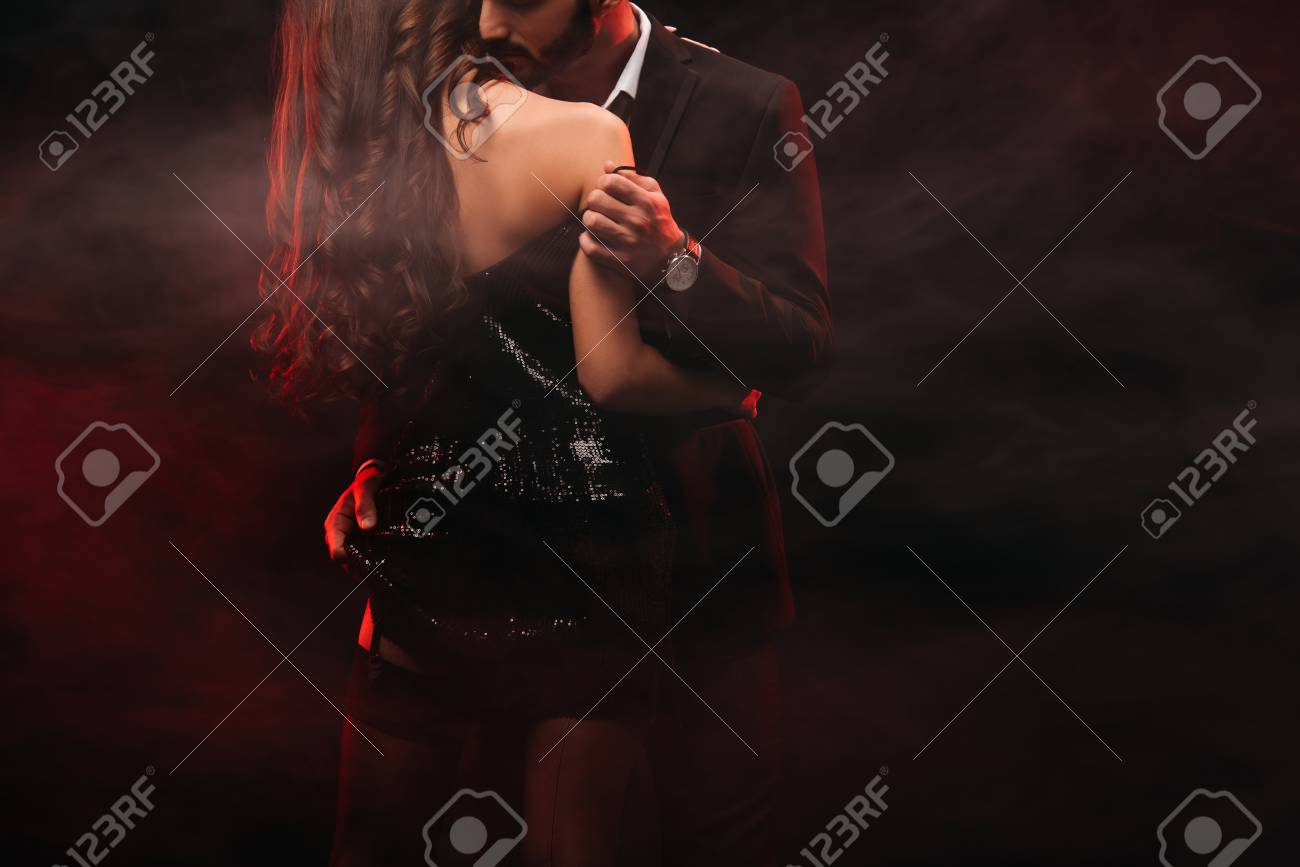cropped view of passionate couple hugging in red smoky room - 118504579