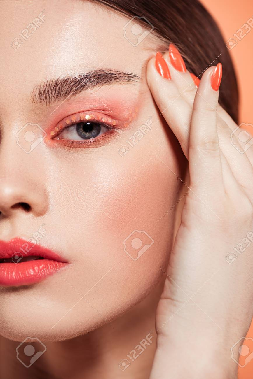 beautiful stylish young woman with glitter makeup looking at camera isolated on coral - 119041932