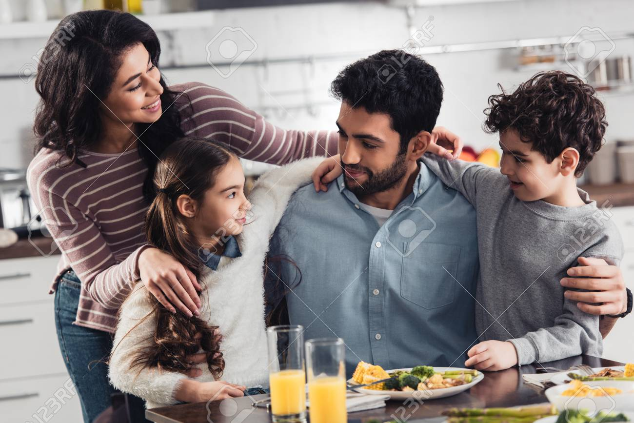 cheerful hispanic family smiling while hugging near lunch at home - 119886327