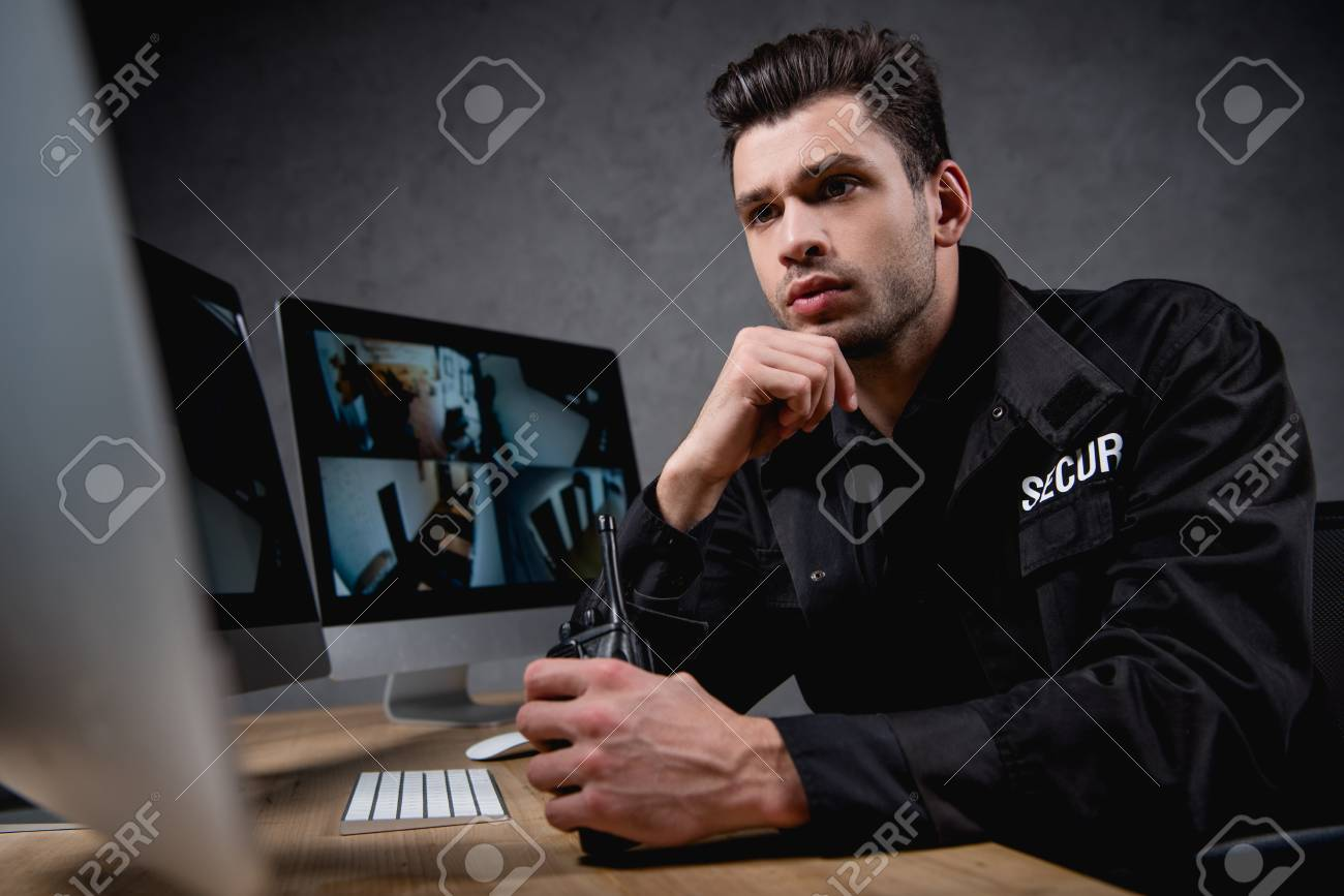 6120bd3a focused guard in uniform looking at computer monitor and holding  walkie-talkie Stock Photo -