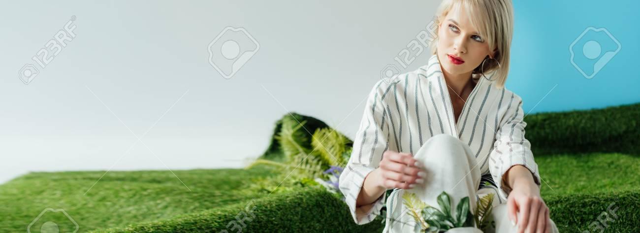 panoramic shot of beautiful stylish blonde girl sitting on artificial grass - 119804381